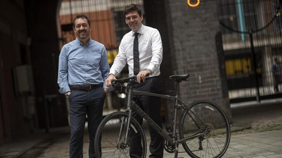 Mayor Andy Burnham holding a bike, standing next to Chris Boardman in a courtyard