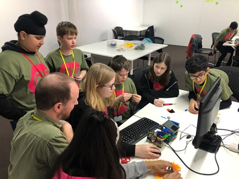 A group of young people all huddled around a computer with a lego robot in front of them